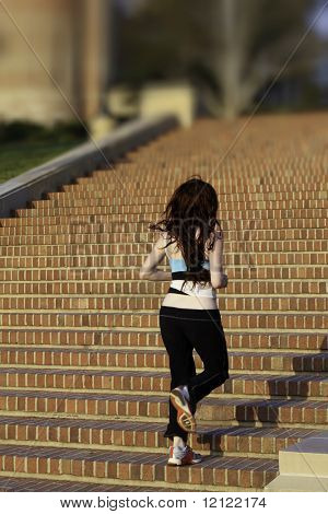 A red haired woman running up brick stairs in workout clothes