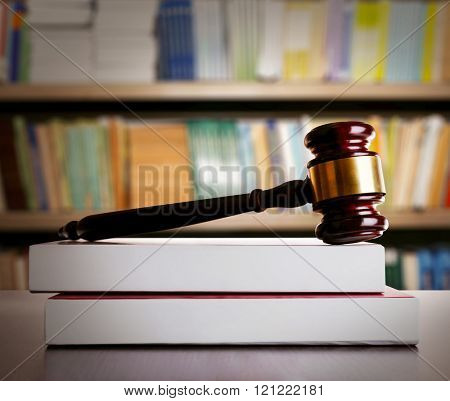 Judge gavel and books on wooden table on book shelves background