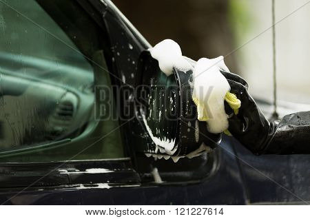 Closeup black rubber gloves working on washing car side mirror with soapy water