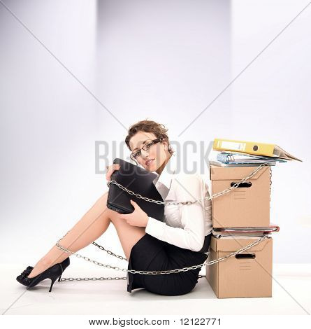 Successful young businesswoman sitting next to pile of documents