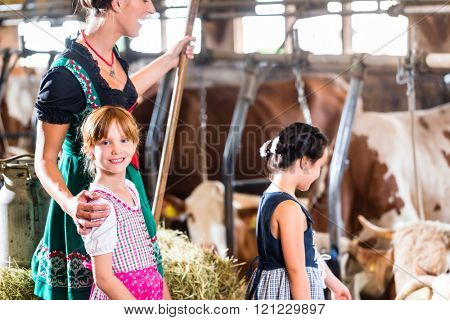 Bavarian mother showing children cows on cow farm