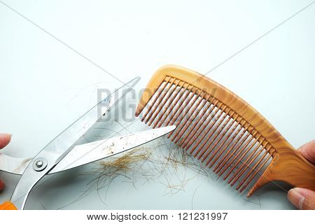 Brown comb and scissors with hair and fingers on gray background.