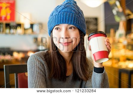 Woman holding coffee at indoor cafe