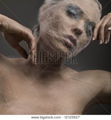 Fine art portrait of a young woman wraped with cowebs