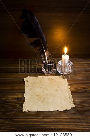 feather, old paper and candle on a wooden background