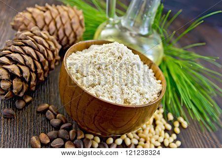 Flour cedar in wooden bowl with oil on board