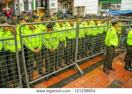 Quito, Ecuador - August 27, 2015: Policemen behind metal fence barrricade awaiting orders during mas