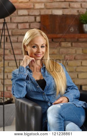 Happy blonde woman smiling, sitting in armchair in jeans.