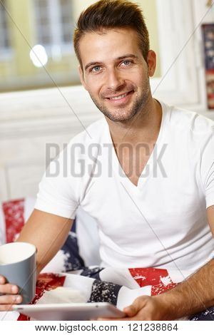 Morning portrait of handsome young man with tea, smiling happy, looking at camera.