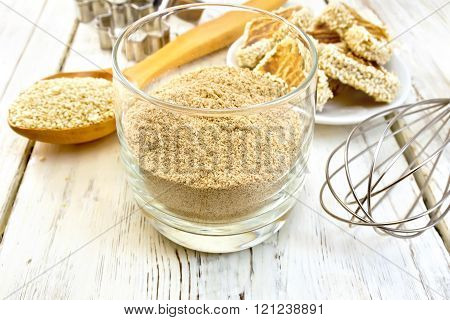 Flour sesame in glassful with spoon on board