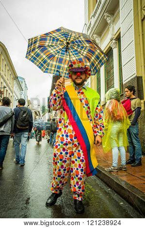 Quito, Ecuador - August 27, 2015: Man dressed up as a clown with umbrella in city streets during mas