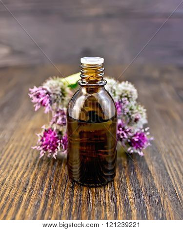 Oil with burdock in vial on board