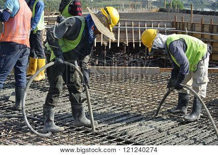 CYBERJAYA, MALAYSIA - MAY 15, 2014: Construction workers using a concrete vibrator at a construction site in Selangor, Malaysia. Concrete vibrator is used for compacting new concrete was cast.