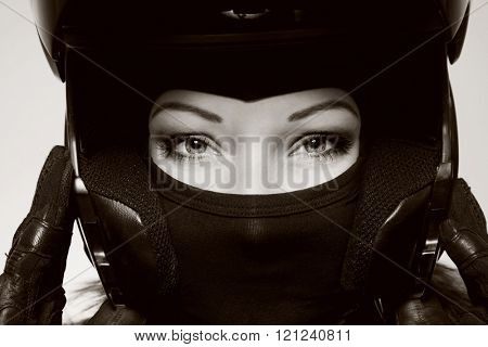 Duotone close-up portrait of beautiful woman with stylish makeup in black biker helmet, mask and gloves