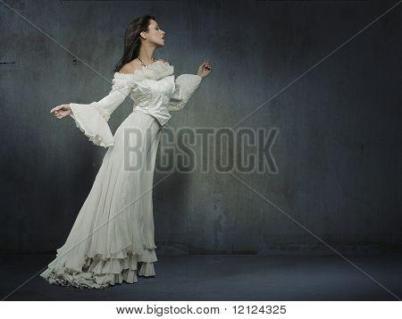 美丽的女人在球衣墙穿白色的礼服