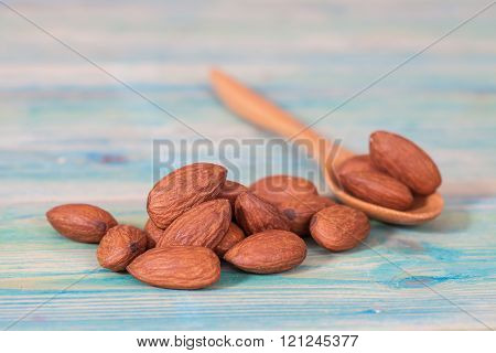 Almonds in wood spoon and all on wood table