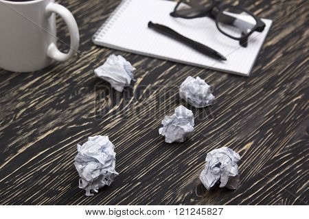 Crumpled paper balls with eye glasses mug, pen and notebook