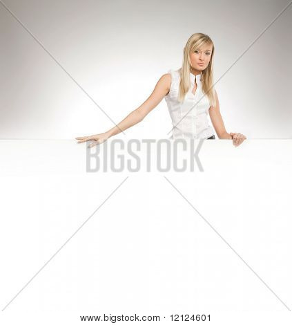 Attractive blonde secretary over white empty board, lots of copyspace