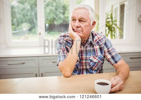 Thoughtful senior man sitting at table with a cup of coffee
