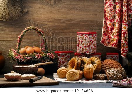 Many mixed bread and rolls on the table in the kitchen