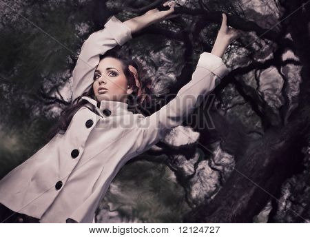 Fine ART style photo of a gorgeous brunette holding branch