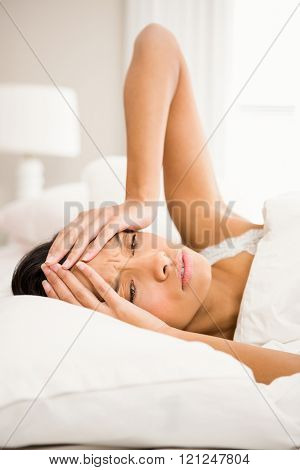 Frowning brunette in bed with hands on face