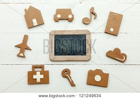 Cardboard web icons and an old blackboard on white background