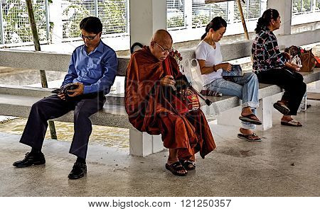 Bangkok, 19.11.2009. Thailand, Bangkok - city people that are reading. On the quay, river water bus station, people sit and read books. Among them, the monk writes something in a notebook recent findings