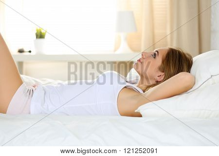 Young beautiful blonde smiling woman portrait wake up early morning after sleeping and lying in bed dreaming. Sweet dreams and good morning, new day, weekend, day off, holidays concept