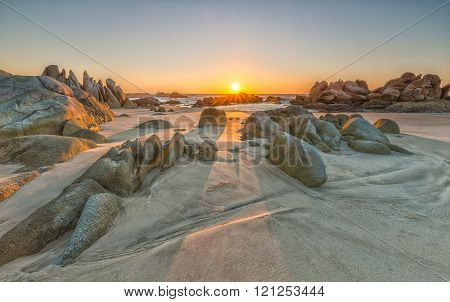 The path of the rock into the sun rises with volcanic rocks on the sand overlooking the sea where the sun was rising star radiating beautiful to watch