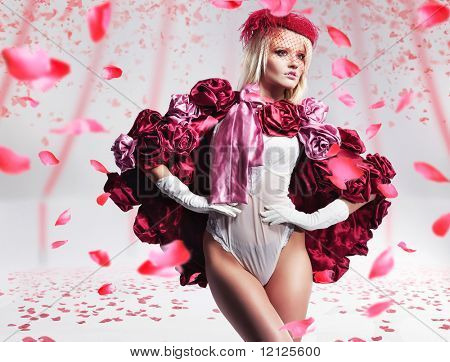 Beautiful blond beauty over flying rose petals