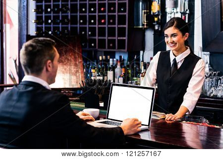 Businessman talking to barmaid and using laptop in a bar