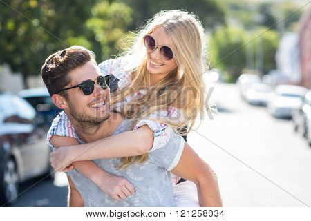 Hip man giving piggy back to his girlfriend on the street