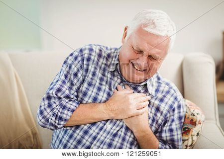 Senior man getting chest pain in living room