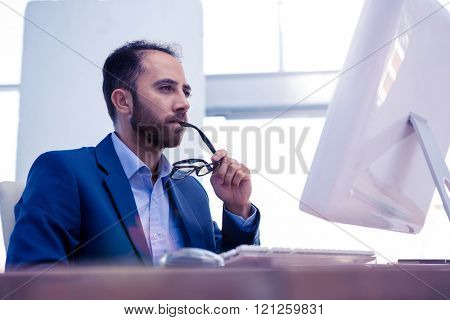 Concentrated businessman holding eyeglasses while looking at computer monitor in office