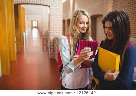 Smiling students using smartphone at university