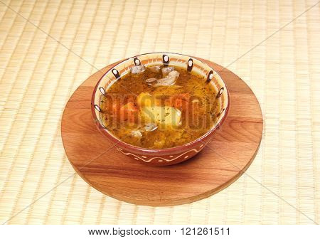 Simple soup with meat and potatoes in a clay plate.