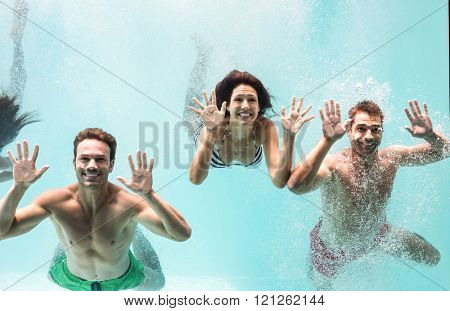 Two couples enjoying and swimming underwater in swimming pool