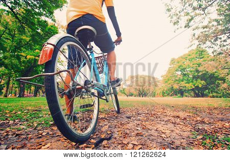 A Young Man Is Cycling Into The Sunset In The Park, In Vintage Retro Tone