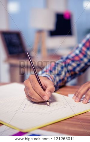 Cropped hand of businessman drawing house in book at desk in office