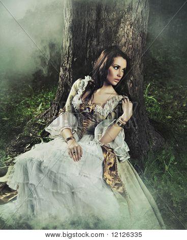 Beleza morena linda em um vestido à moda antiga em uma floresta
