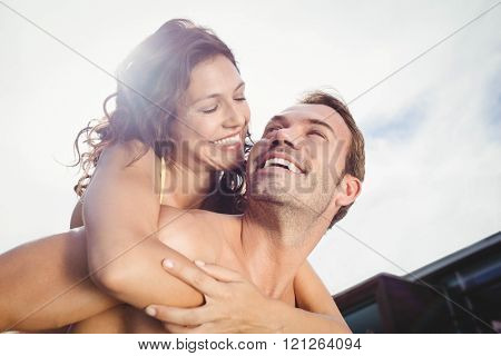 Close-up of man giving piggy back to woman near poolside on a sunny day