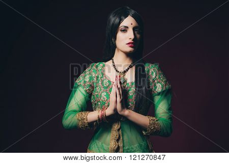 Traditional Bollywood Fashion Woman Against Dark Red Background.
