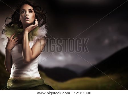 Beauty brunette posing over dark sky background