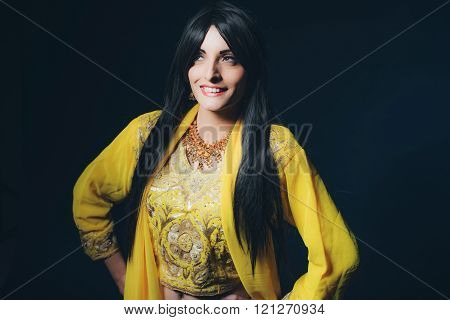 Smiling Vintage Bollywood Fashion Woman In Yellow Clothing Against Dark Blue Background.