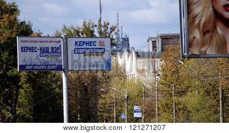 KHARKOV, UKRAINE - CIRCA OCTOBER 2015: Two billboards of the one mayoral candidate depicting historical places of Kharkov next to each other on the background of the workshop building, autumn sky and autumn trees.