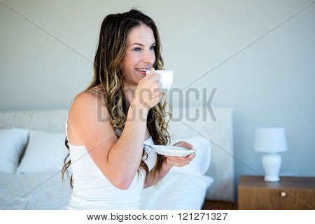smiling woman sipping a cup of coffee on her bedside
