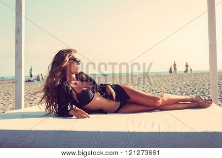 attractive tanned young woman in black bikini and shirt lie on beach bed at sand sea  beach, summer sunny day full body shot