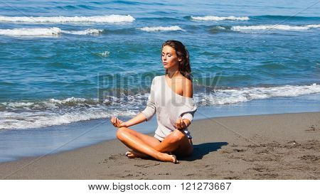 young woman meditate on sandy  beach by the sea full body shot sunny summer day