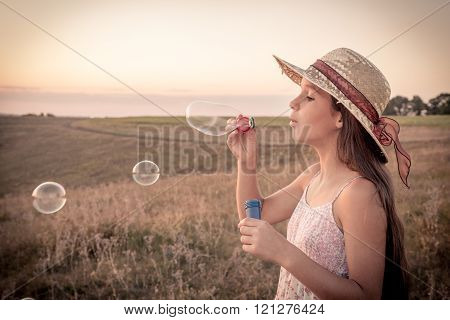 Girl blowing up the soap bubbles